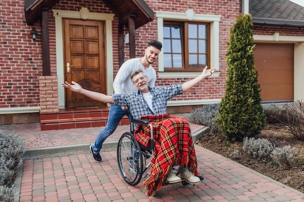 Padre senior in sedia a rotelle e giovane figlio su una passeggiata vicino alla casa di cura.