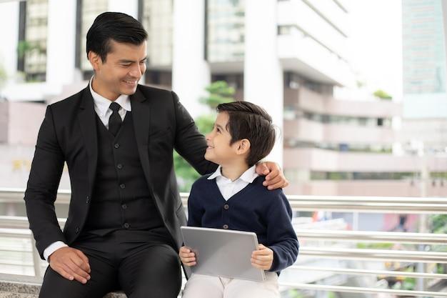 Padre single e figlio che giocano insieme gioco smart phone sul quartiere degli affari urbano