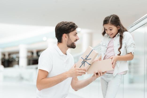 Padre sta aprendo un nuovo regalo per la ragazza dalla borsa della spesa.