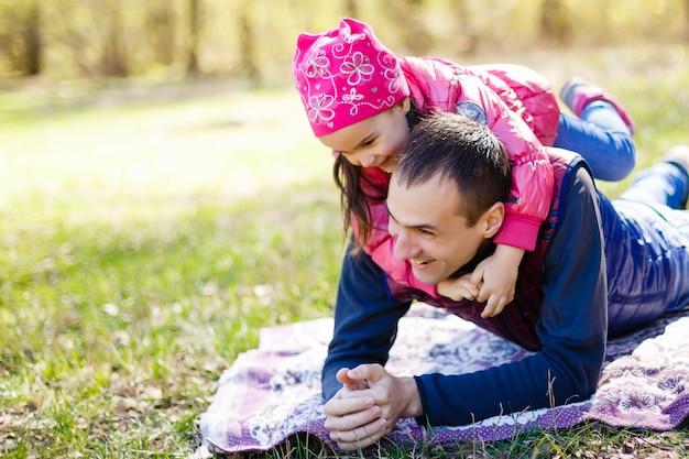 Padre votato e figlia che si trovano sull'erba