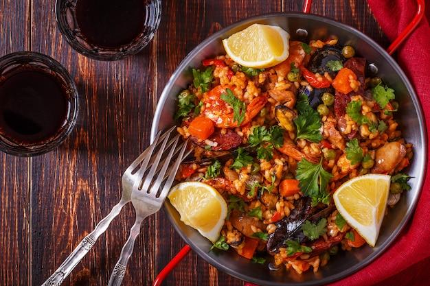 Paella con pollo, chorizo, frutti di mare, verdure e zafferano servita nella padella tradizionale.