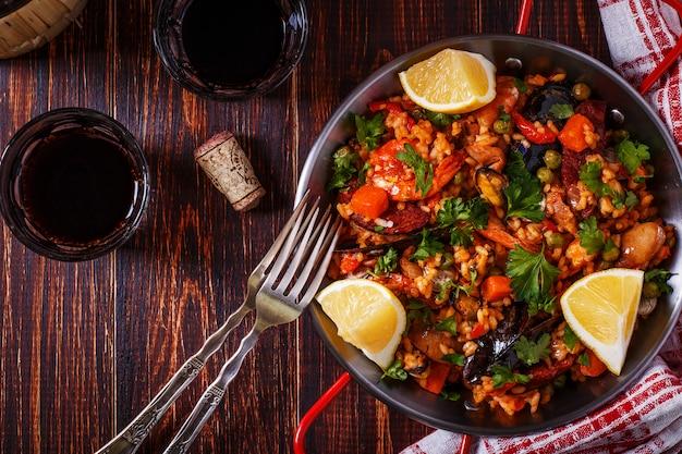 Paella con pollo servita in padella tradizionale