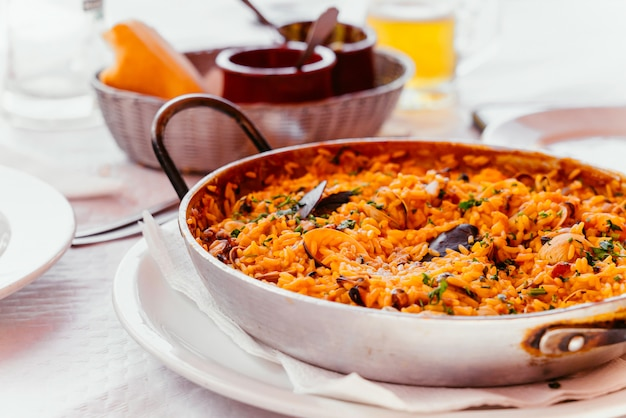 Paella di pesce spagnola con cozze, gamberi, ecc. in una padella per paella d'acciaio. cucina delle isole canarie in un piccolo ristorante di famiglia.