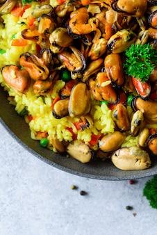 Paella di pesce spagnolo tradizionale in padella riso, piselli, gamberetti, cozze, calamari