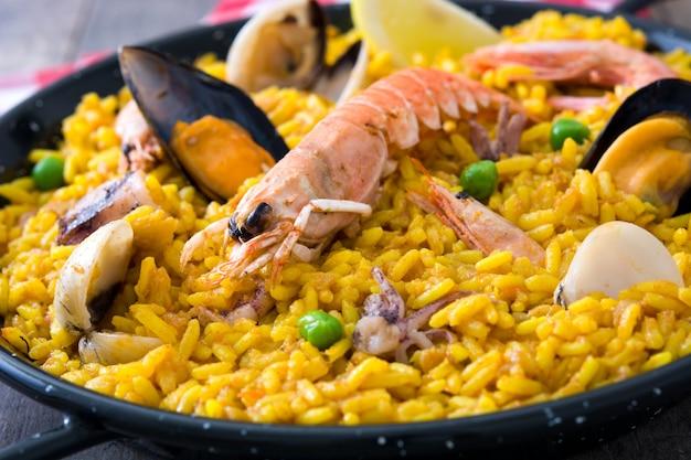 Paella spagnola tradizionale dei frutti di mare sulla fine di legno della tavola su