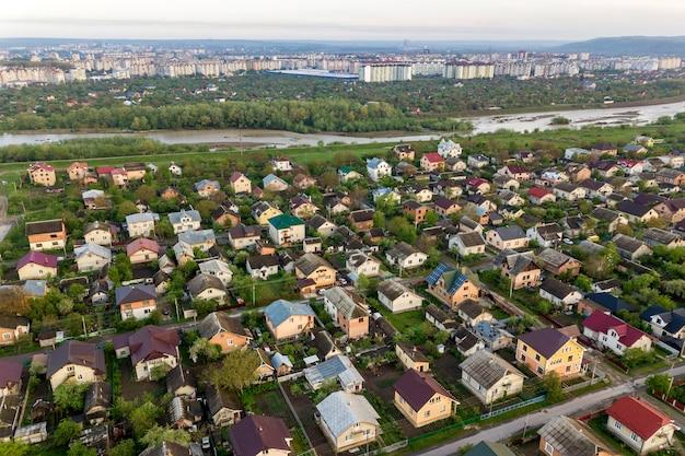 Paesaggio aereo della cittadina o del villaggio con filari di case residenziali e alberi verdi.