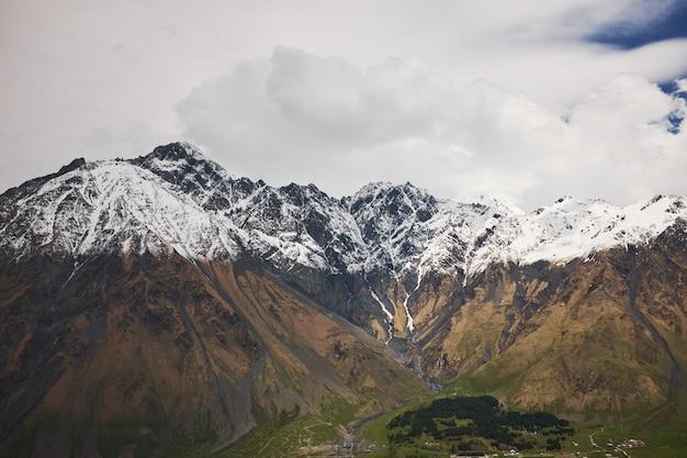 Paesaggio autunnale di montagna con alte cime innevate e cielo blu con nuvole