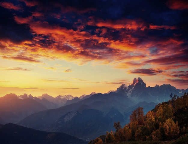 Paesaggio autunnale e cime innevate. tramonto fantastico