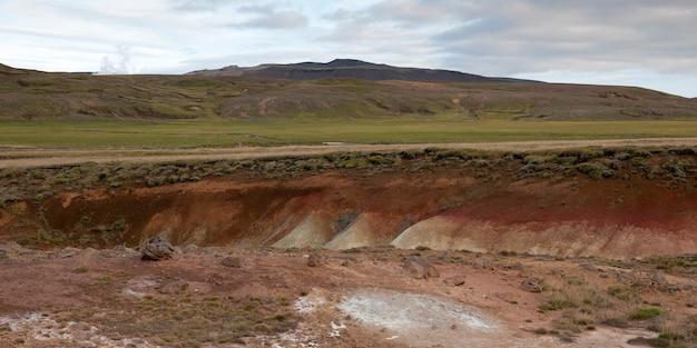 Paesaggio, burrone ricco di minerali erosi attraverso prati, prima di montagne erbose