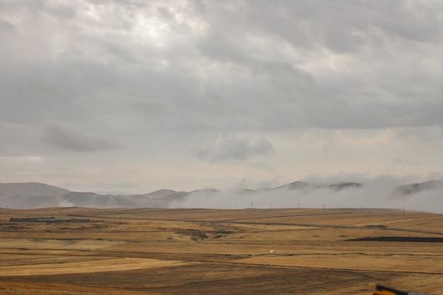Paesaggio circondato da alte montagne sotto le nuvole di tempesta