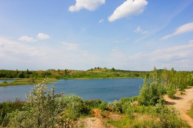 Paesaggio con fiume, alberi verdi e nuvole