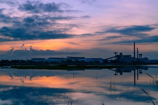 Paesaggio degli edifici industriali di fabbrica con il riflesso del cielo al tramonto blu scuro e arancione sull'acqua nel fiume.