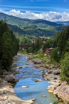 Paesaggio dei carpazi, montagne, alberi, fiume e ponte contro il cielo blu