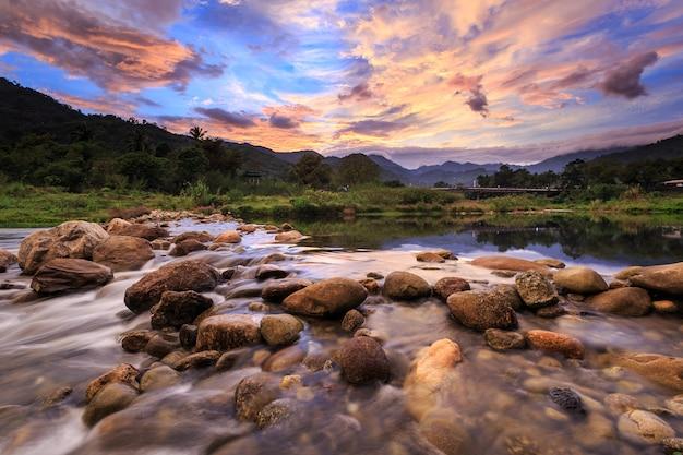 Paesaggio del piccolo fiume e bel tramonto nel villaggio di kiriwong. la migliore posizione di ozono a thaila