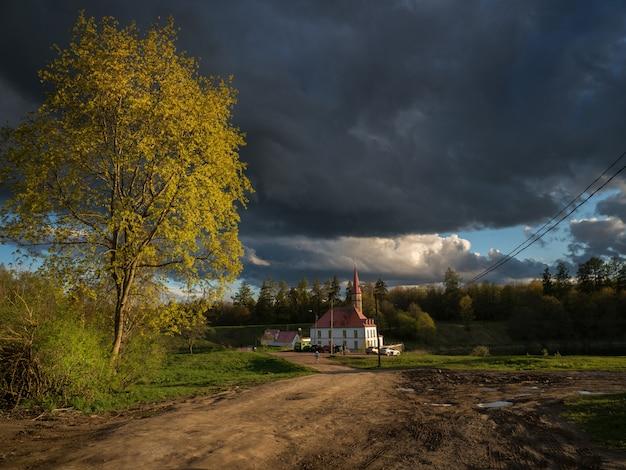 Paesaggio della campagna di sera con le nuvole di pioggia drammatiche e il