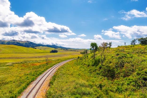 Paesaggio della campagna e della ferrovia con le colline verdi ed il cielo blu