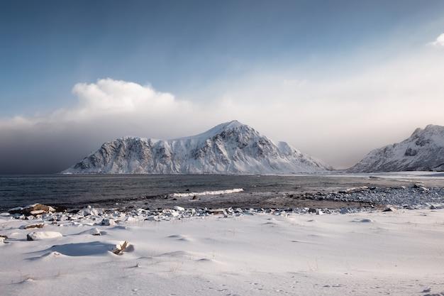 Paesaggio della catena montuosa della neve con il cielo nuvoloso in inverno