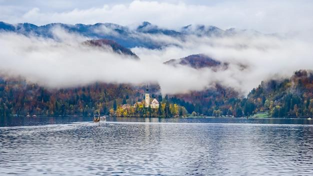Paesaggio della chiesa del lago sanguinato in un giorno nebbioso sull'autunno in slovenia