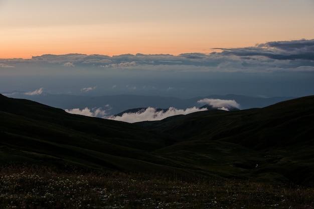 Paesaggio della collina coperta di erba nei precedenti del cielo nuvoloso nel tramonto