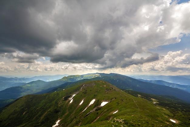 Paesaggio della cresta della montagna sotto l'ampia vista panoramica drammatica del cielo nuvoloso, dell'estate o della primavera.
