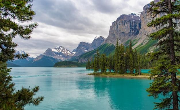 Paesaggio della foresta del canada dell'isola di spirito con la grande montagna nei precedenti, alberta, canada.