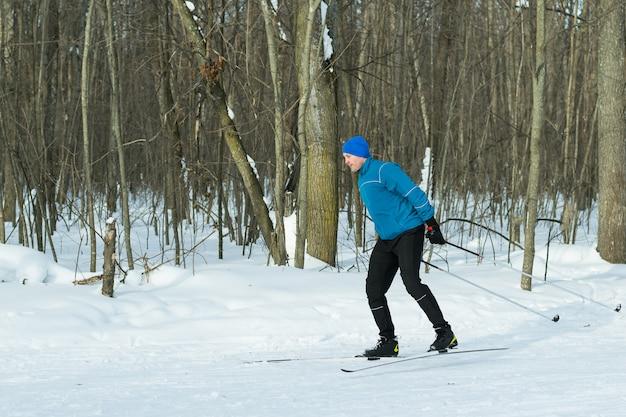 Paesaggio della foresta invernale con uno sciatore in esecuzione.