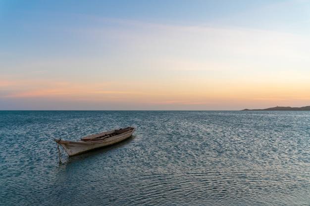 Paesaggio della spiaggia tropicale di paradiso, alba, tramonto sparato, con una barca