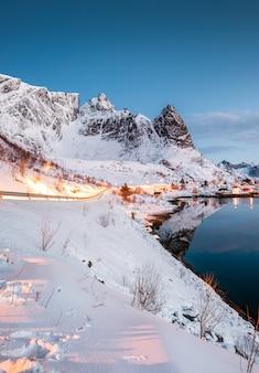 Paesaggio della strada che emette luce sulla montagna nel paesino di pescatori norvegese alla linea costiera artica