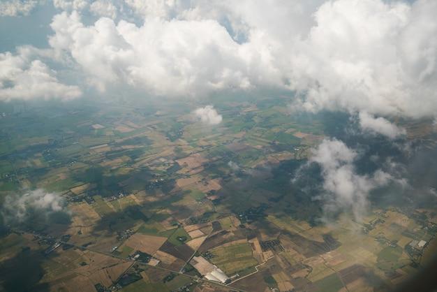 Paesaggio della terra visualizzato dall'aeroplano. superficie terrestre sotto le nuvole bianche dalla vista aerea.