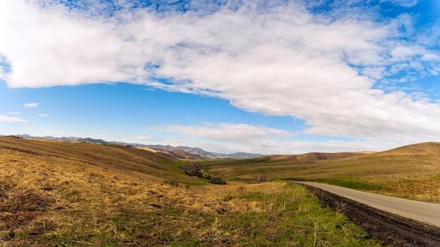 Paesaggio delle alte montagne dell'altai del distretto di chemal all'inizio della primavera con boschi di conifere e betulle e la strada, il cielo è coperto di nuvole