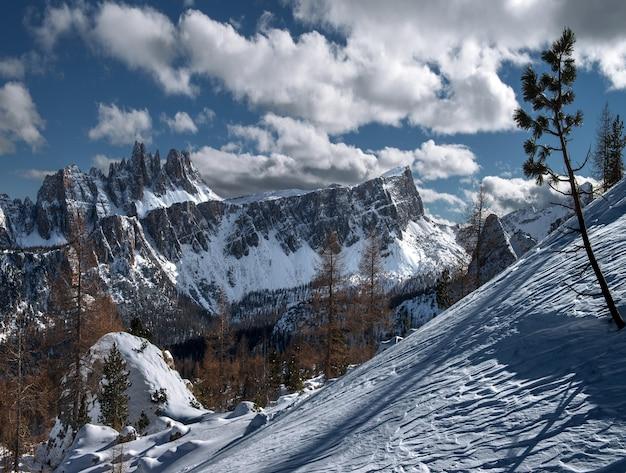 Paesaggio delle dolomiti coperte di neve sotto la luce del sole nelle alpi italiane