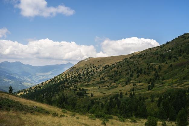 Paesaggio di colline ricoperte di vegetazione con montagne rocciose sotto un cielo nuvoloso sul