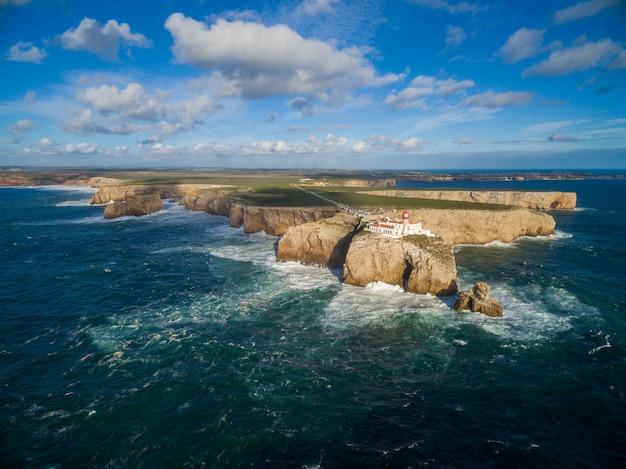 Paesaggio di colpo alto di un'isola con un palazzo su esso circondato dal mare sotto un cielo blu nel portogallo