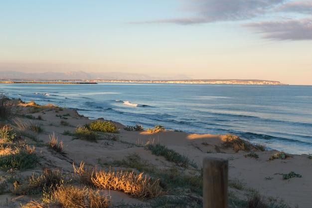 Paesaggio di dune di sabbia sulla spiaggia al tramonto vicino al mare con nuvole scure nel cielo e il villaggio sullo sfondo