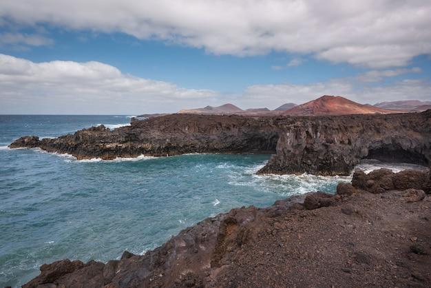 Paesaggio di lanzarote costa di los hervideros, grotte di lava, scogliere e oceano ondulato.