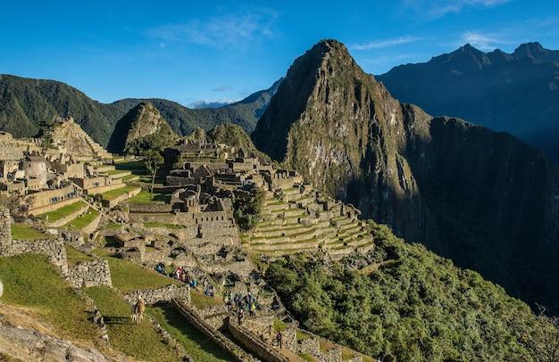 Paesaggio di machu picchu sotto la luce del sole e un cielo blu in perù