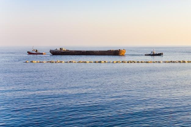 Paesaggio di mare con rimorchiatori che trasportano una chiatta