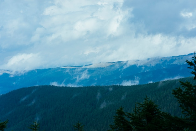 Paesaggio di montagna a strati nel cielo blu nebbia con nuvole