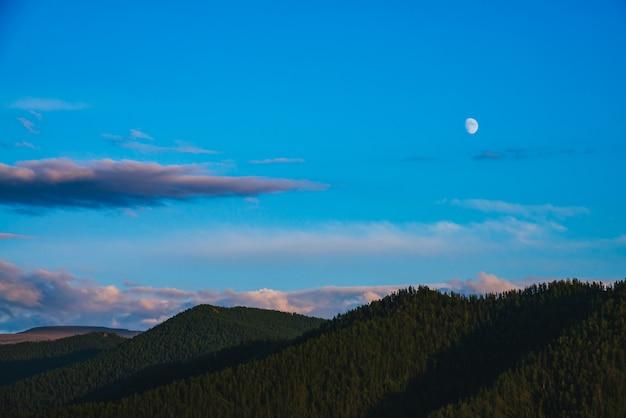 Paesaggio di montagna minimo con grandi montagne forestali sotto il cielo blu con nuvole viola e luna sul tramonto.