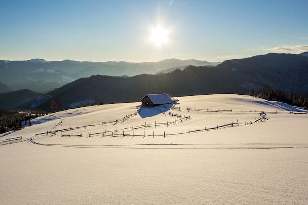 Paesaggio di natale di inverno della valle della montagna il giorno soleggiato gelido. vecchia capanna abbandonata di legno del pastore in neve pulita profonda bianca, cresta di montagna scura legnosa, sole luminoso