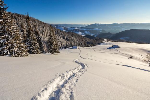 Paesaggio di natale di inverno della valle della montagna il giorno soleggiato gelido.