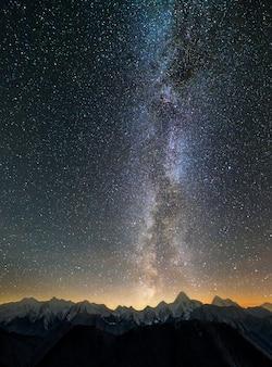 Paesaggio di panorama notturno di montagna invernale. ripide vette ricoperte di neve e foresta di abeti rossi, illuminata dal sole che tramonta sotto il cielo stellato blu scuro e la luminosa costellazione della via lattea.