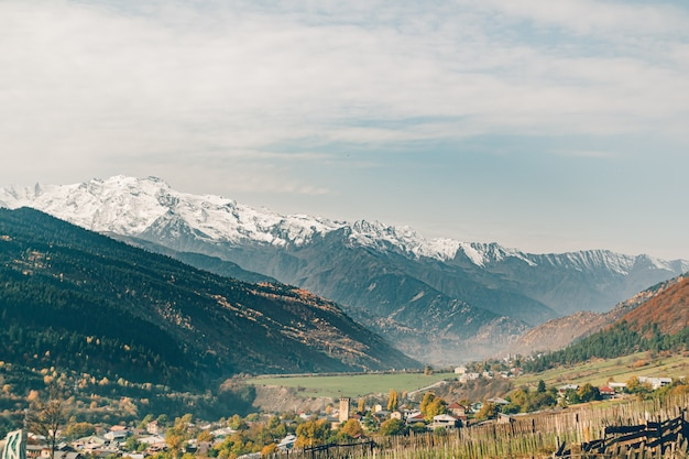 Paesaggio di piccola città rurale di mestia nella valle con la montagna della neve della georgia.