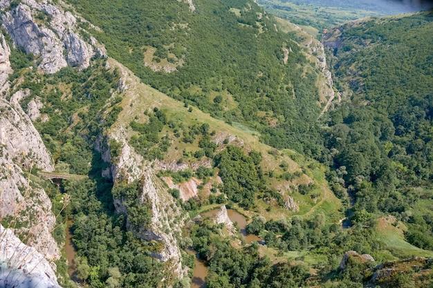 Paesaggio di rocce ricoperte di vegetazione sotto un cielo blu e la luce del sole
