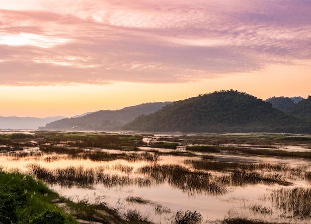 Paesaggio di tramonto del fiume mekong inaridito in tailandia del nordest.