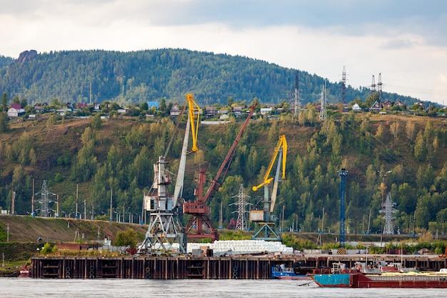 Paesaggio di un'enorme costruzione industriale: diverse gru di lavoro sul fiume, chiatte con carico e su uno sfondo di una città industriale con piccole case