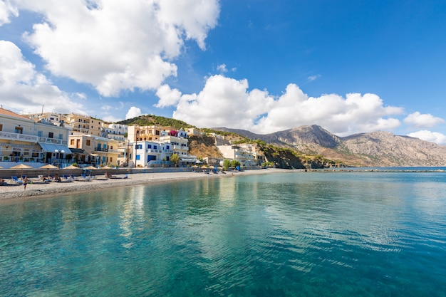 Paesaggio di un mare circondato da montagne edifici e spiagge sotto un cielo nuvoloso blu in grecia