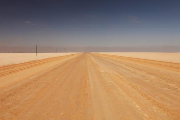 Paesaggio di una strada in un deserto sotto la luce del sole alla luce del giorno