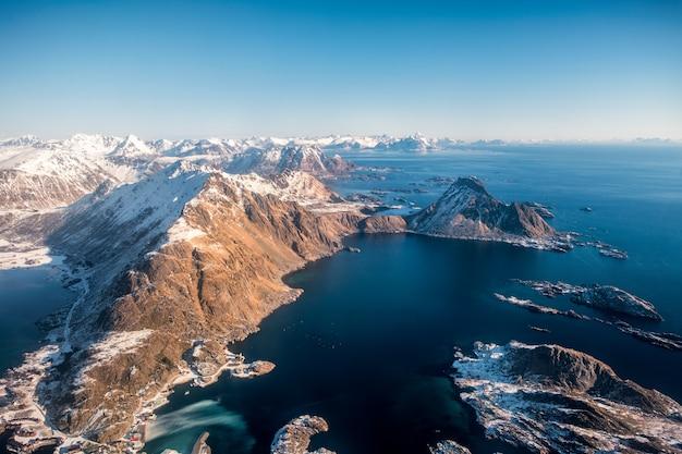 Paesaggio di vista aerea delle montagne circondate nella linea costiera dell'oceano artico con cielo blu