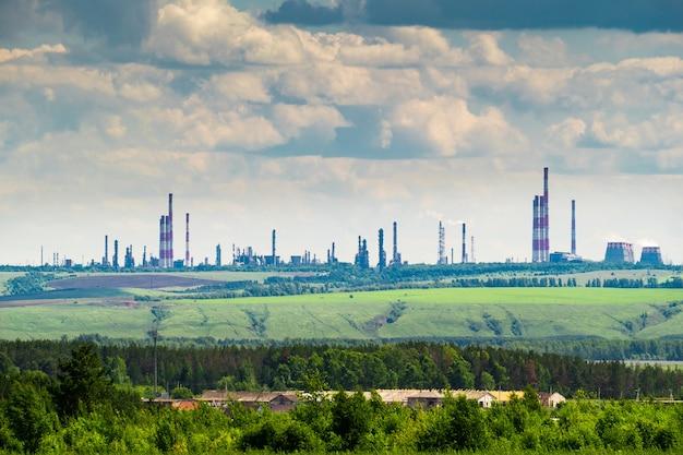 Paesaggio industriale con una raffineria di petrolio sulla collina verde